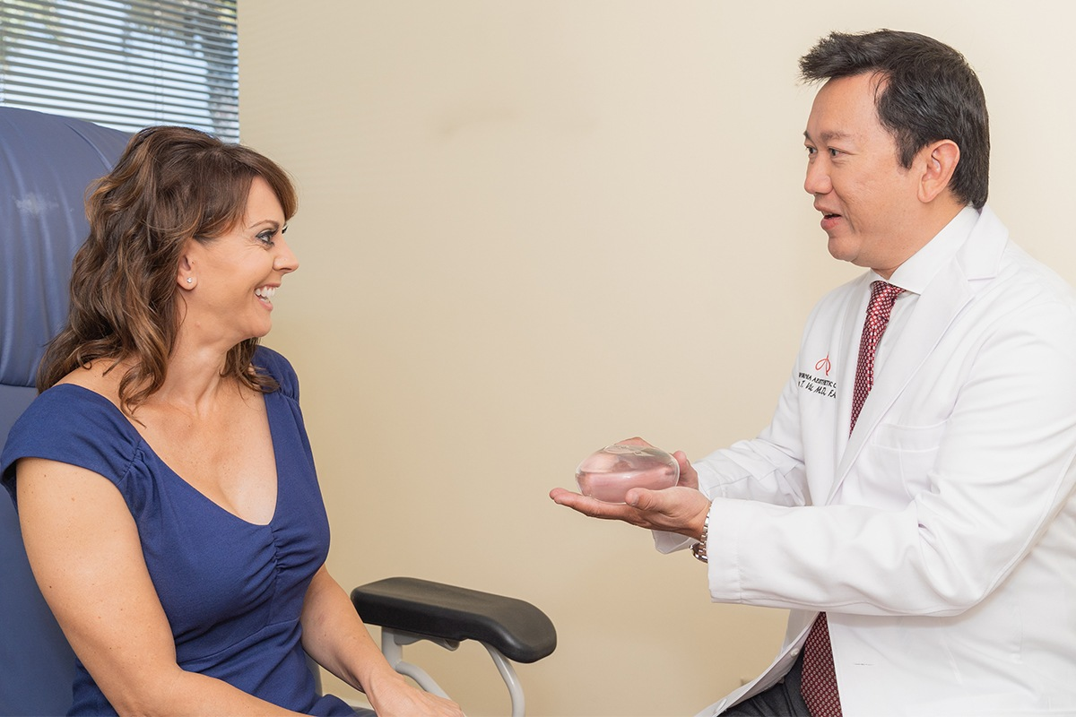 Dr. Vu Showing A Female Patient A Breast Implant During Consultation