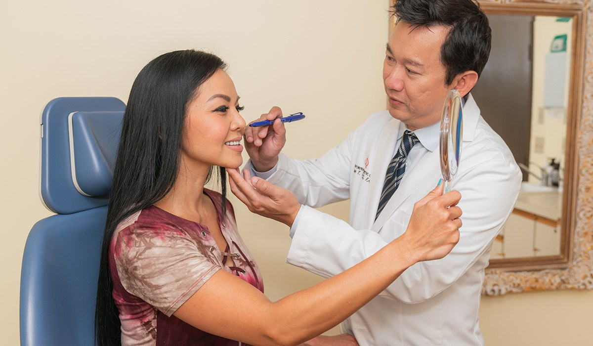 Dr. Vu Using Marker On Female Patient's Face During Consultation